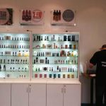 Evapo Ashford shop interior. Glass cabinets holding eliquid and promotional posters over the top
