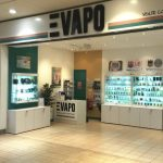exterior view of vape shop with products in glass cabinets and sign above